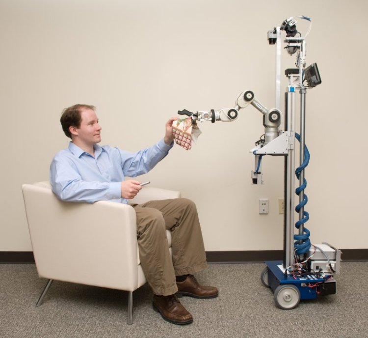 Photo of the mobile manipulator EL-E delivering an object to Charlie Kemp.